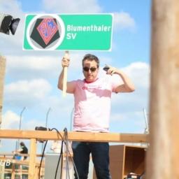 Arnd Zeigler hält bei der DFB-Pokal Auslosung ein Schild des Blumenthaler SV hoch